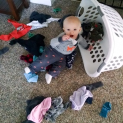Helping mama by sorting his laundry.